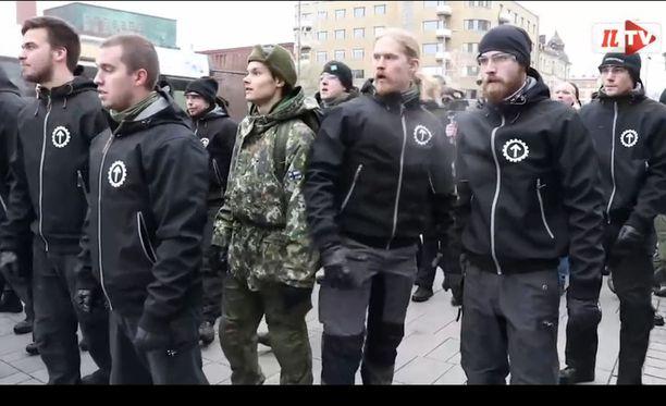 Kuvakaappaus videolta, jossa näkyy sotilaspuvussa Pohjoismaisen vastarintaliikkeen jäsenten kanssa mielenosoituksessa marssiva varusmies.