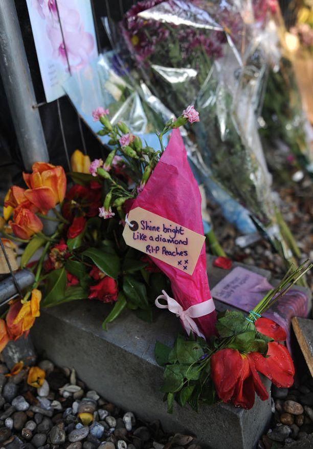 Hautajaiskirkon liepeille oli tuotu paljon kukkia.