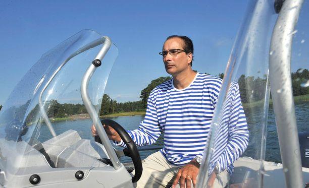 Heikki Lampela veneilee kesämökilleen. Vuosi on 2010, ja tyylinä tällä kertaa ajaton Marimekko.