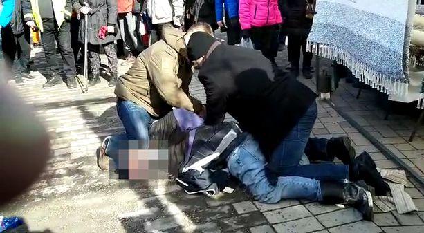 Hyökkääjä joutui kahden miehen hallintaotteesen. Ainakin toisella kiinniottajalla oli poliisin virkamerkki.