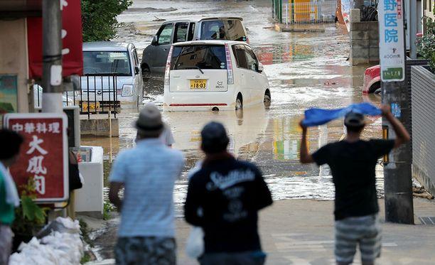 Fuchun kaupungin asukkaat katselevat kuinka tulva vie mukanaan autoja.