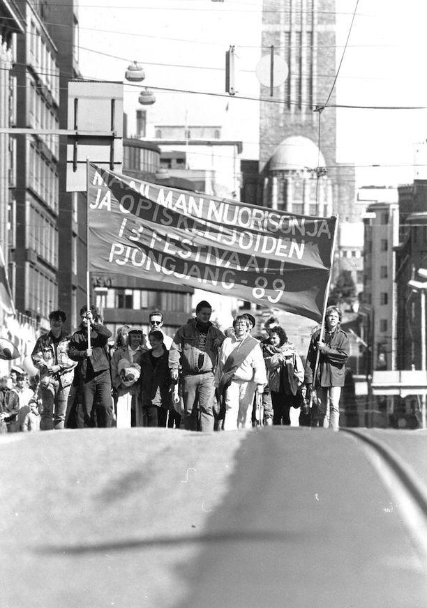 """""""Hakaniemestä Senaatintorille marssi noin 4 000 kansandemokraattia ja kommunistia. Aikataulu oli järjestetty siten, etteivät demarit tulleet samaan aikaan vastaan,"""" kerrottiin lehdessä vappuna 1989. Kuvan kyltissä mainostettiin Pohjois-Korean Pjongjangissa järjestettyä Maailman nuorison ja opiskelijoiden festivaalia."""