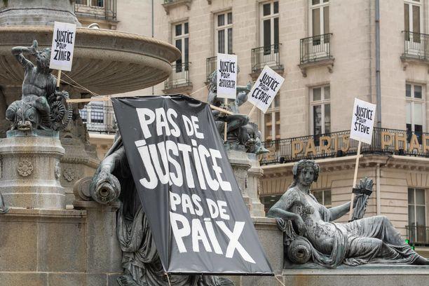 Cédric Chouviatin nimi näkyy kylttien joukossa, joita on viety Nantesin keskusaukiolle. Kylteissä vaaditaan oikeutta väkivallan uhreille.