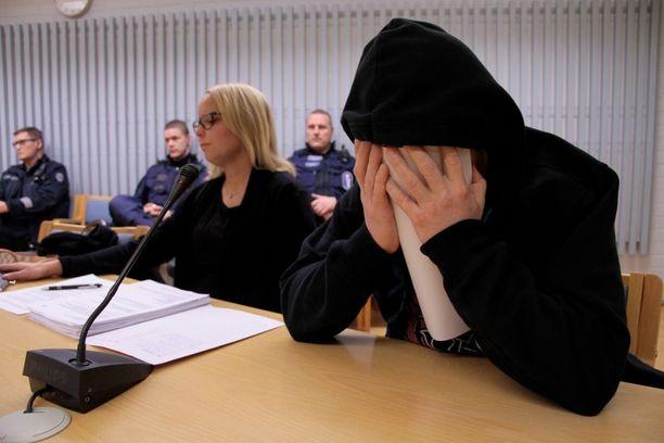 Syytetty mies peitti kasvonsa istunnon alussa.