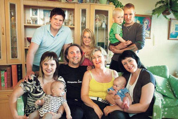 """Keskellä istuva Kristiina Ketola-Orava,49, on äiti, äitipuoli, sijaisäiti, mummo ja mummopuoli. Aviomies Pasi Orava, 48, kutsuu häntä Neitokaiseksi. Kuvassa vasemmalla avopuolisot Make, 26, ja Jenna, 22, jolla on sylissään viisi kuukautta vanha Kasper. Jenna on Pasin biologinen tytär. Jenna kutsui alussa Kristiinaa Reisi-Krisseksi ja Kreisi-Krisseksi. Oikealla avopuolisot Ville, 26, ja Mira, 25, ja pariskunnan lapset Eemeli, 4 v, ja Rasmus 4 kk. Mira on Kristiinan biologinen tytär. Ville kutsuu avoanoppiaan Risuliiniksi. Takana Kaisa, 11, joka tuli Pasin ja Kristiinan perheeseen """"ovesta, ei mahasta""""."""