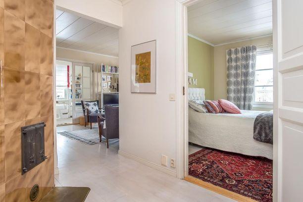 Kodissa on usea huone ja kakluuni. Taaempana näkyy myös avaraa tunnelmaa luovat pariovet.