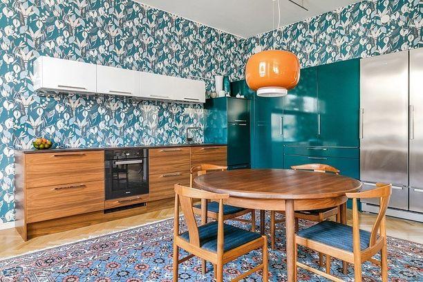 Kuviollinen tapetti sävytettynä turkooseihin kaapistoihin ja sinipunaiseen mattoon, tuo kodikasta tunnelmaa. Puuta, terästä, valkoista pintaa ja räväkkää väriä - rohkeat yhdistelmät toimivat yllättävän hyvin.