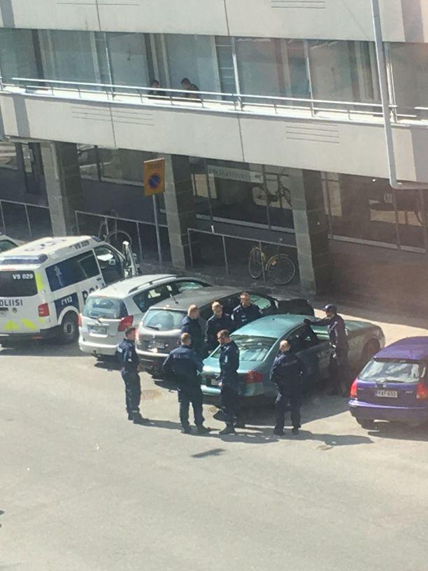 Poliisi tutki autoa, josta löytyi käsiase. Kaksi otettiin kiinni.