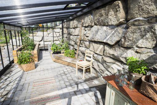 Villa Sukan alapihalla on olotilaksikin soveltuva kasvihuone. Alue on pengerretty vanhoilla kivijalkakivillä. Asuntomessukohde 9.