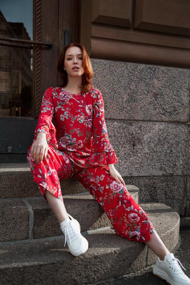 Kokovartaloasun ei tarvitse olla jakkupuku, vaan se voi olla myös pusero ja housut -yhdistelmä. Kirkkaanpunapohjainen kukkaprintti herättää juuri sopivasti ihailevaa huomioita.