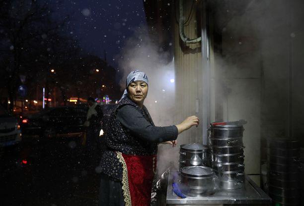 Uiguurinainen hoitaa ruokakojuaan Urumqin kaupungissa Xinjiangin provinssissa. Noin 45 prosenttia provinssin asukkaista on uiguureja.