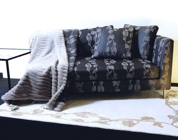 DIVAANI. Matossa ja kankaassa toistuu sama Art Deco -kuvio. HT-Collectionin sohva on päällystetty Lennolin kankaalla, matto VM-Carpet. Turkis ei ole aitoa.