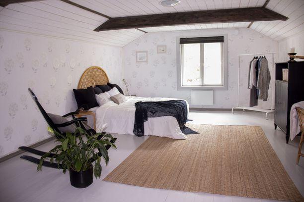 Talossa on useita makuuhuoneita. Tästä yläkerran makuuhuoneesta ei maalaisromantiikkaa puutu.