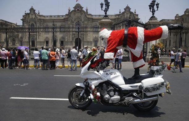 Perulainen pukki temppuilee taitavasti moottoripyörän päällä. Muina vuodenaikoina tämä herra työskentelee liikennepoliisina.