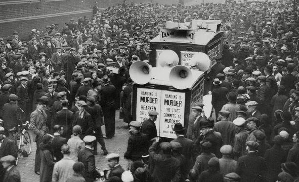 Yleisö parveili kovaäänisten lähettyvillä 12. toukokuuta vuonna 1936 saadakseen tietoa Buck Ruxtonin kuolemantuomion toimeenpanosta.