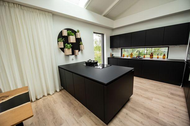 Messutalossa on vetimetön keittiö, jonka mattamusta väri tuo kontrastia talon vaaleisiin seinäpintoihin. Välitilassa on ikkuna, mikä tekee tiskaamisestakin hauskempaa. Lisäksi keittiön ilme muuttuu sen avulla vuodenaikojen mukaan.
