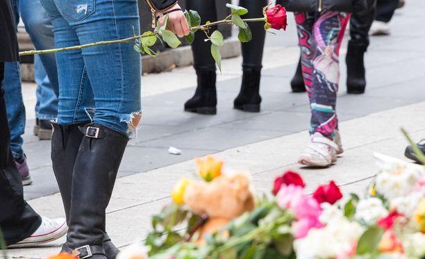 Tukholman Drotninggatanille ohikulkijat jättävät kukkia terrori-iskussa kuolleiden muistoksi.