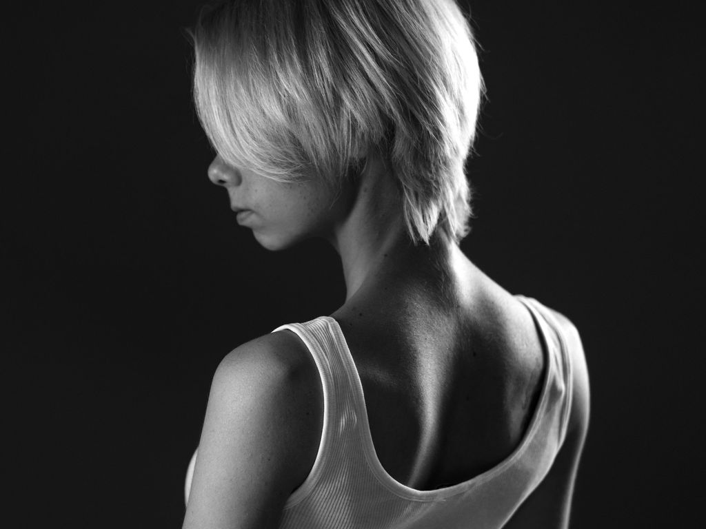 A young sad woman looks away, a dark black and white photo. Stands sideways .