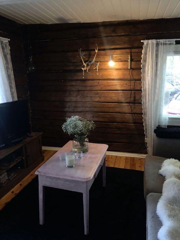 Olohuoneen sohvaa koristavat valkoiset lampaantaljat. Valkoiset pitsiverhot ja vaalea pöytä tuovat raikkautta tilaan.