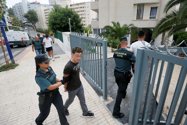 Poliisi vei ranskalaismiehiä rakennukseen, jossa väitetty raiskaus tapahtui.