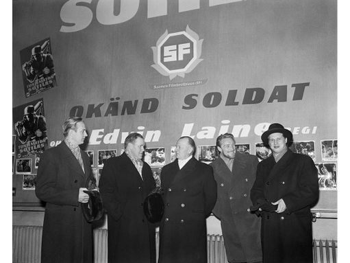 """Suomalaisen sotaelokuvan """"Tuntematon sotilas"""" ensi-ilta elokuvateatteri Bio Rexissä 19. joulukuuta 1955. Elokuvan tekijöitä ryhmäkuvassa. Vasemmalta Kosti Klemelä (luutnantti Koskelan rooli), elokuvan ohjaaja Edvin Laine, kenraaliluutnantti P. A. Autti (JR 8:n ensimmäinen komentaja, kutsuvieras), Åke Lindman (alikersantti Lehdon rooli) ja Reino Tolvanen (alikersantti Rokan rooli). Taustalla Suomi-filmin logo."""