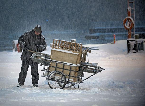 Kauppatorille pyrytti lisää lunta illansuussa.