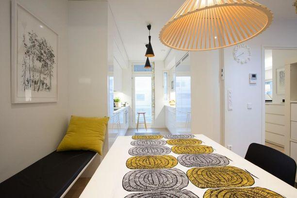 Keittiöön on tuotu värejä pöytäliinan ja tyynyn avulla.