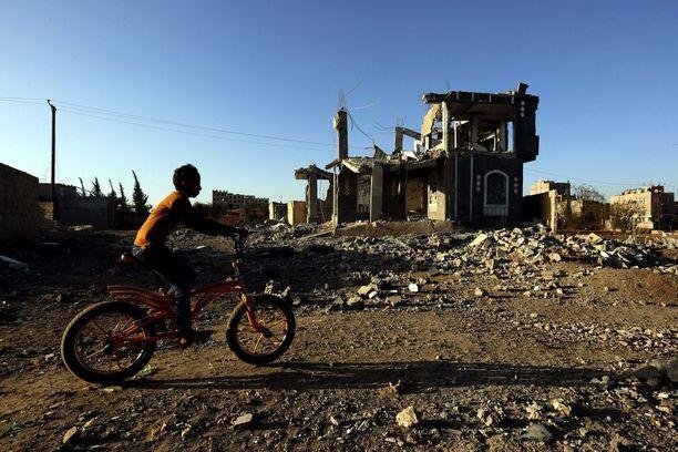 Poika pyöräili ilmaiskussa tuhotun rakennuksen ohi viikonloppuna pääkaupunki Sanaassa.