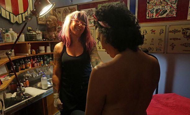 Soracin asiakas, rintasyövästä selvinnyt Melissa McHale ihastelee uutta tatuointiaan.