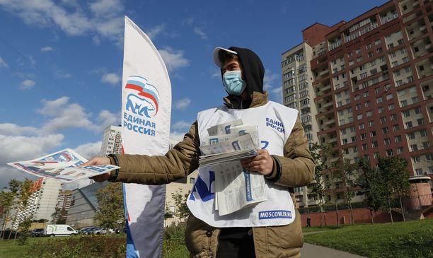 Mies jakeli Putinin puolueen vaalimateriaaleja Moskovassa keskiviikkona.