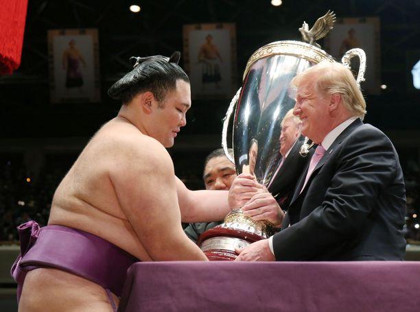 """Donald Trump ojensi valtiovierailullaan sumopainiturnauksen voittajalle Asanoyamalle """"Presidentin maljan"""" Tokiossa 26.5.2019."""