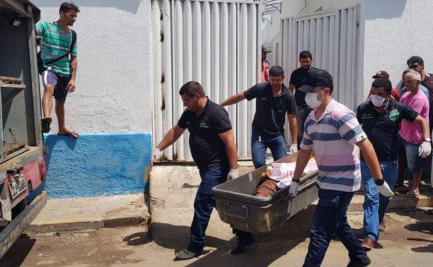 Miehet kantavat ammuskelussa kuolleen ruumista tapahtumapaikalta perjantaina aamulla paikallista aikaa.