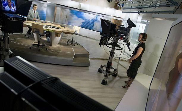Arkistokuva Ylen studiosta. Nykyinen viestintäpäällikkö Jere Nurminen on pöydän takana.