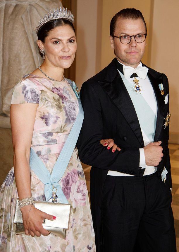 Kruununprinsessa Victoria luotti vaaleaan, kukalliseen asuun. Vierellä puoliso Daniel.