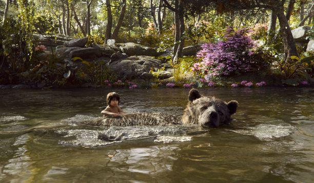 Mowgli-poika ja tietokonegrafiikalla toteutettu Baloo-karhu uiskentelemassa Viidakkokirjan uusintaversiossa.
