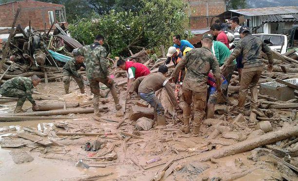 Sotilaat kaivavat ihmisiä esiin mudasta.