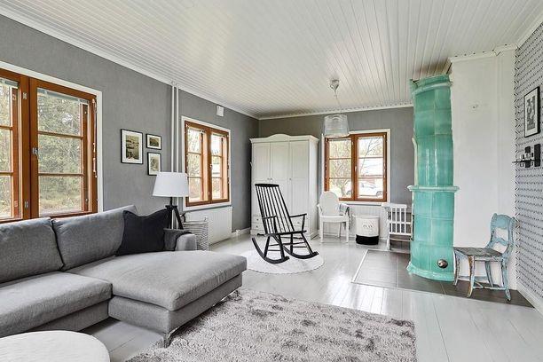 Maalaisromanttisen tunnelman voi toteuttaa myös näin. Harmonia rakentuu harmaista sävyistä ja huoneen ehdoton katseenkiinnittäjä on turkoosi kakluuni.