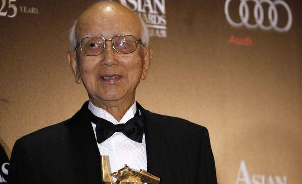 Elokuvatuottaja Raymond Chow poseeraa kuvassa elokuva-alan palkintopysti kädessään Hong Kongissa maaliskuussa 2011.