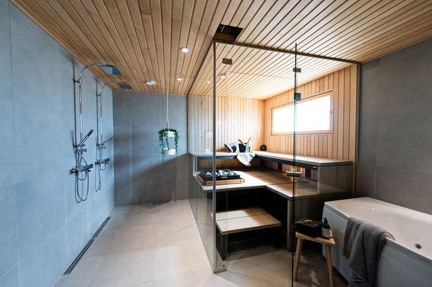 Opn Kotoisa -kohteen saunassa lauteiden mustat alaosat tuovat ilmeeseen mukavasti kontrastia. Lasiseinät keventävät kokonaisuutta.