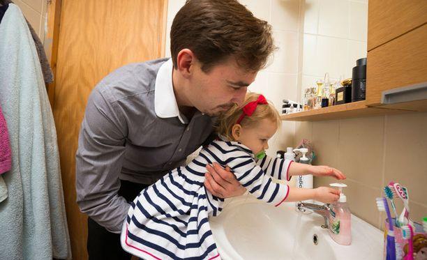 Isla, 2, pesee miellään käsiään. Seurana Arttur-isä.