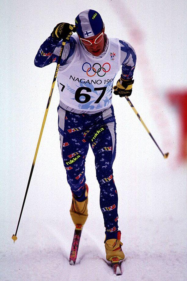 Harri Kirvesniemi hiihti tutusti pää kenossa, värikäs asu päällään Naganossa 1998.