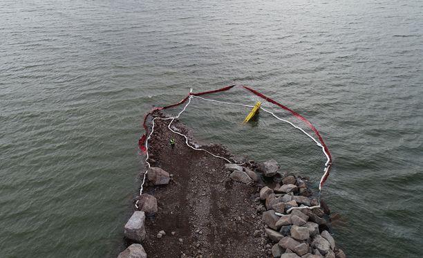 Mereen uponnut kaivinkone on aidattu öljypuomein.