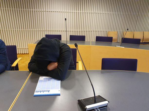 Miestä syytetään useista rikoksista. Hän peitti kasvonsa medialta oikeudessa.