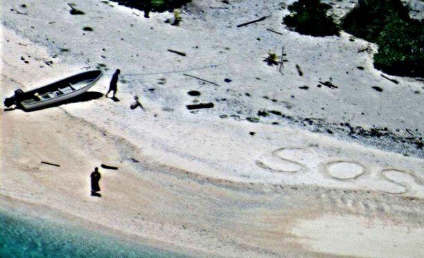 Yli lentänyt helikopteri huomasi hiekkaan piirretyn SOS-merkin.