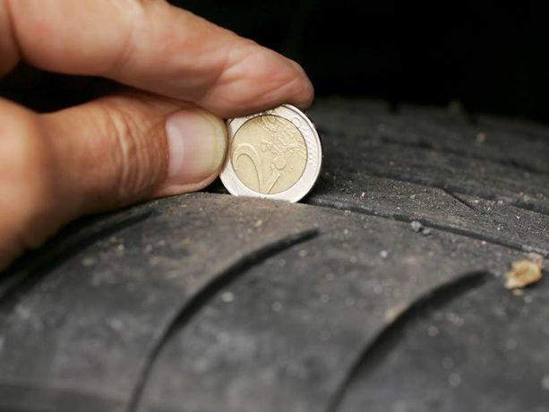 Kahden euron kolikkotesti. Jos kolikon reunaa jää näkyviin, kuten kuvassa, ura on liian matala turvalliseen ajoon.