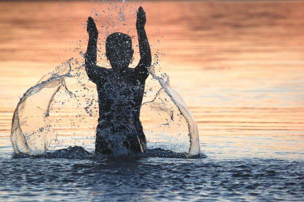Uimari kesäillassa Pielisellä kolin vaarojen kupeessa.