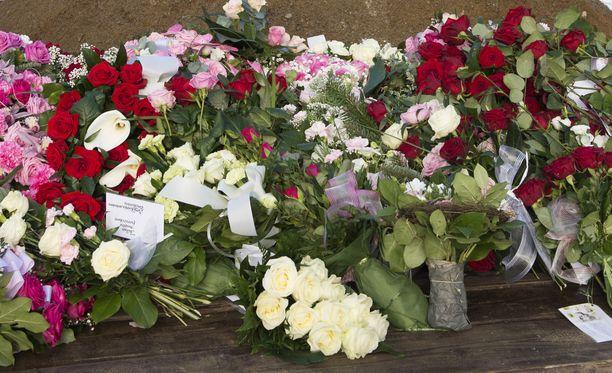 Kukkia ja surunvalitteluja haudalla. Kuvituskuva.
