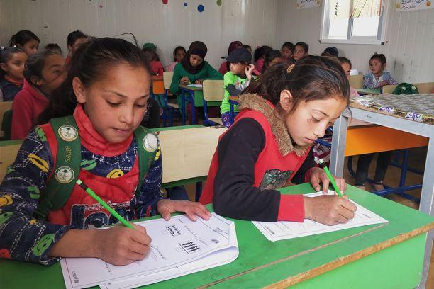 Azraqin pakolaisleirissä sijaitsevassa Makaani-koulutuskeskuksessa luokallinen oppilaita valmistautuu kokeeseen. Keskittynyttä tunnelmaa ei riko edes toimittajan saapuminen, vaan tytöt hädin tuskin vilkaisevat häiritsijää.