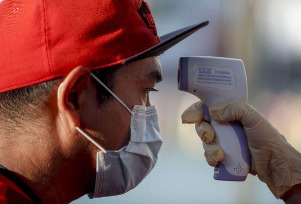 Eri puolilla maailmaa on ryhdytty toimiin tartuntojen ehkäisemiseksi. Tässä kuvassa näkyy, miten mieheltä mitattiin kuumetta Singaporessa perjantaina.