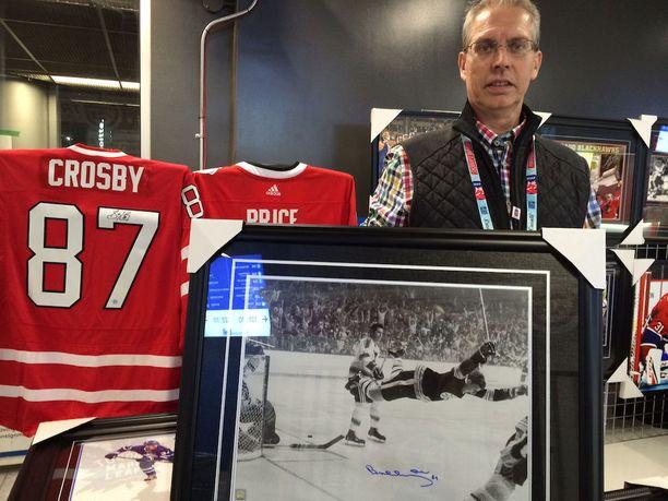 Jacques Gingras myy Canadiens-fanituotteiden ohella muutakin NHL:ään liittyvää tavaraa. Tässä kuuluisassa Bobby Orr -kuvassa on mukana nimmari.